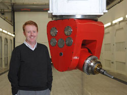 John Weller (PhD '96) standing next to a 5-axis milling machine