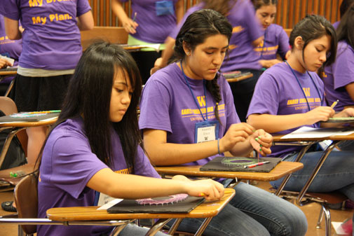 young women in purple shirts at desks