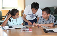 a mentor works with two students on a small electrical device