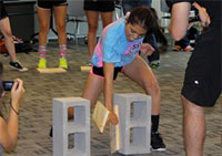 girl breaks a board suspended between cinder blocks