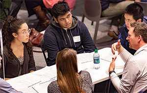 students and alumna in discussion at Engineering Exploration Night