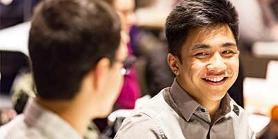 one student smiling at another at a networking event