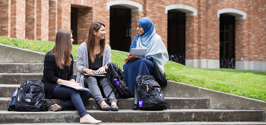 a group of students sitting outdoors chatting