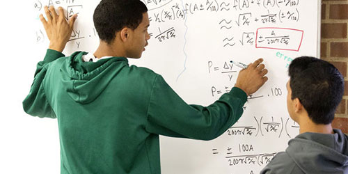 students working on equations at a whiteboard