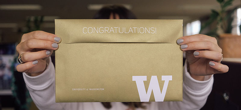 photo, student holding up gold UW admission envelope