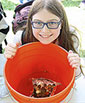 smiling girl with orange 5-gal bucket with floating pennies
