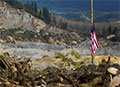 aftermath of Oso landslide with flag at half staff