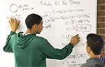 Devin Pegues, left, and Casiano Atienza work on a math problem at a whiteboard at UW