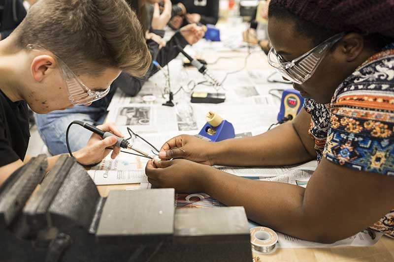 picture of students soldering at a table
