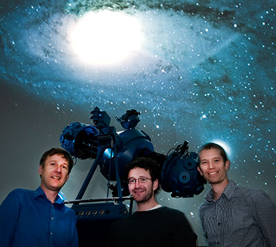 astronomy researchers in front of telescope with 3.2-billion-pixel camera for detecting asteroids