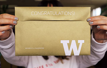 future student holding UW admission notification envelope