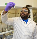 David Coven holds up and inspects a vial in a lab