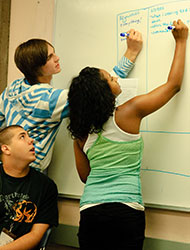 students in class writing on board