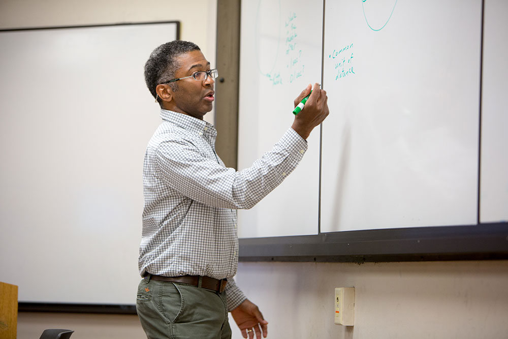 instructor writing on a whiteboard