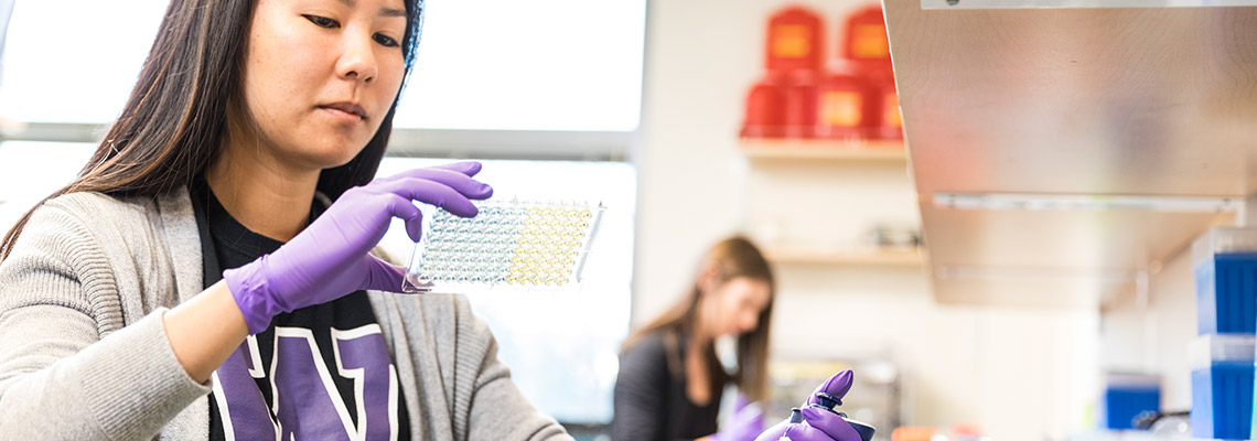 Student looking into samples while using gloves