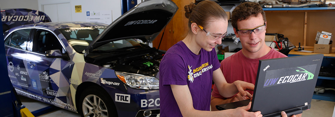 Two students looking at laptop working on ecocar project
