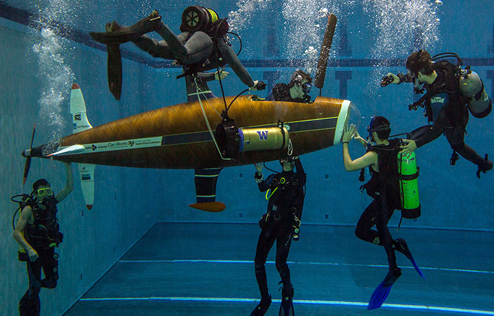 Students underwater working on submarine
