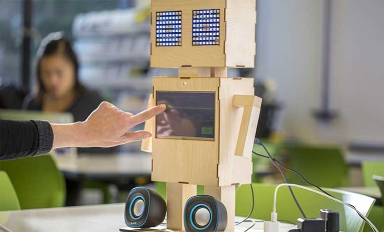 A friendly looking robot clad in wood with a touch screen