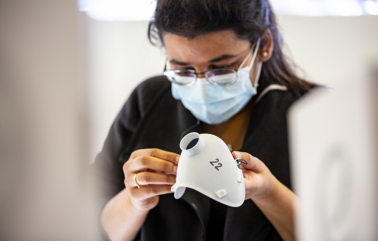 A student looking at a 3D printed medical mask prototype