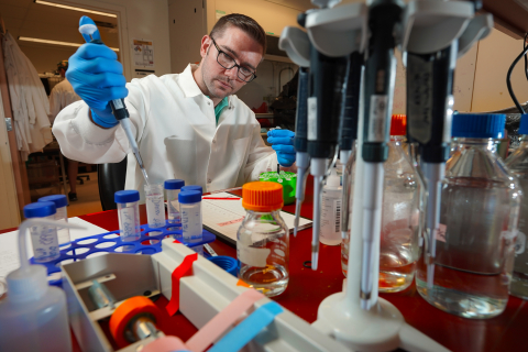 Man in lab coat working with tubes and bottles in a lab