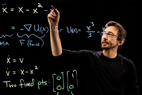 Brunton writing math equations on a lightboard with a marker