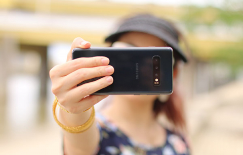 woman holding in a smartphone in front of her face