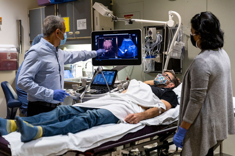 Mike Averkiou pointing at a monitor that shows a contrast-enhanced ultrasound of Lutz's liver while Barry Lutz is lying in bed with Dr. Manjiri Dighe standing at his left
