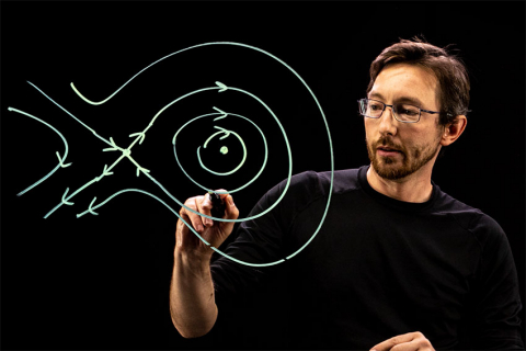 Professor Steve Brunton drawing lines with arrows on a lightboard