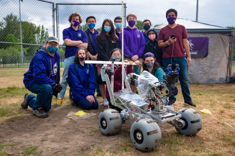 A crowd of 12 people in masks stand in a group outdoors behind a robot that looks like a mars rover