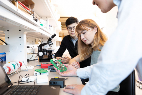 Three students inspecting the inner workings of a device