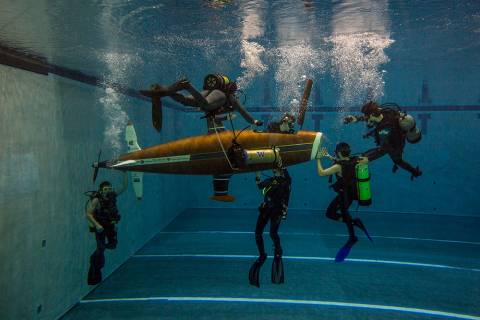 A group of students underwater surrounding a human-powered submarine