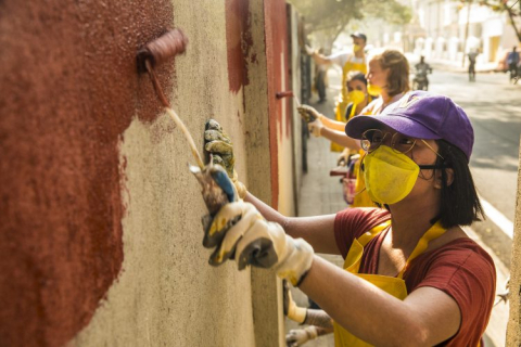 students painting an external wall