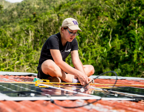 Pozzo installing a solar panel on the roof of a house in Jayuya, Puerto Rico