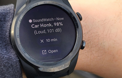 """A wrist with a smartwatch on it. The smartwatch has an alert that says """"Car honk, 98%, Loud, 101 dB"""" It also has options to snooze the alert for 10 minutes or open in an app on the user's phone"""