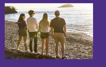 a group of young people standing on a beach