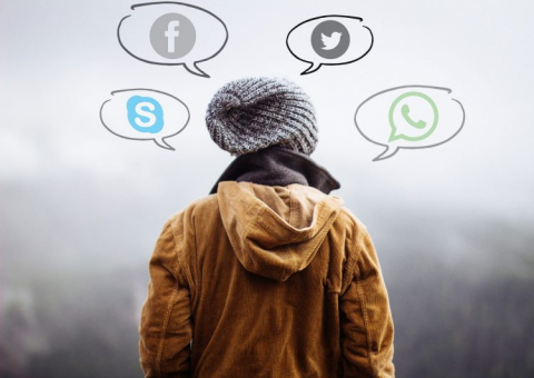 The back of a person wearing a hat and a jacket. Drawn around the person's head are four speech bubbles: Each one contains a logo for either Skype, Facebook, Twitter or WhatsApp