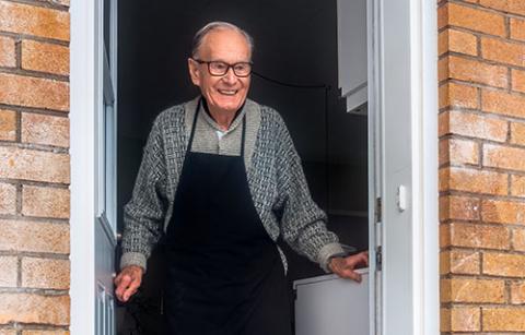 elderly man standing in a doorway