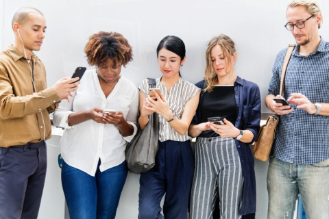 A group of people looking at their phones