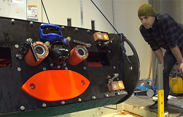 Paul Gibbs, a mechanical engineer at the UW's Applied Physics Laboratory, inspects the newest Adaptable Monitoring Package, or AMP, before a test in a saltwater pool.