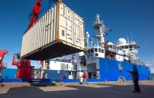 freight shipping container in foreground and research ship in background