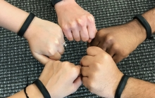 Five hands making fists in a circle. All arms have black Fitbit trackers on them.
