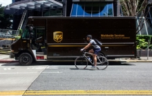 bicycle rider and delivery truck trying to share space on an urban road