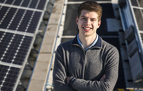 CEE student Alex Ratcliff standing in front of solar panels